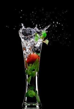 View of soft drink splashing out of glass on black back