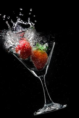View of martini glass with strawberry on black background