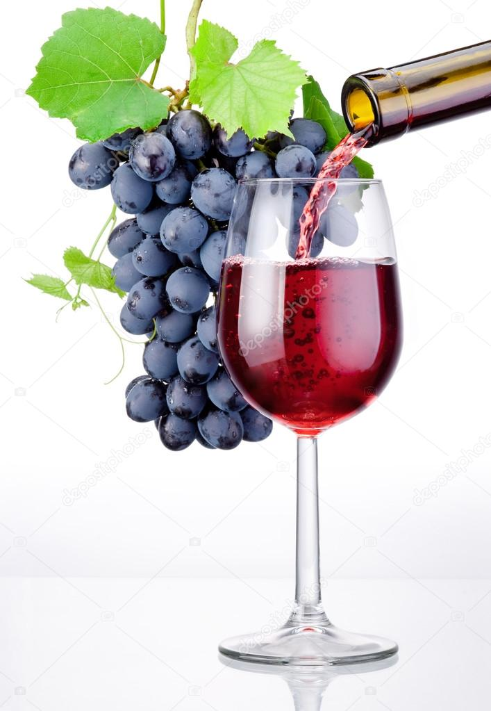 Pouring a glass of red wine and bunch of grapes with leaves isol