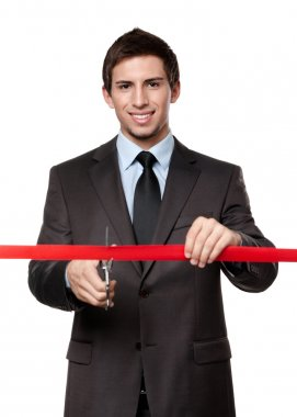 A man cutting a red ribbon with scissors