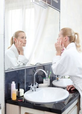 Young girl in bathrobe looks at the mirror