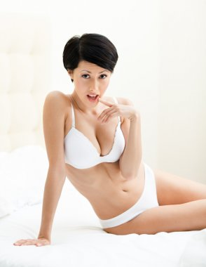 Halfnaked woman sits on the double bed