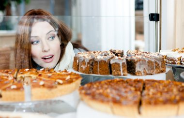 Girl in scarf looking at the bakery showcase