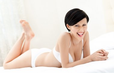 Woman in white underwear is lying in the queensize bed