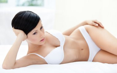 Woman in bra is lying in the comfortable bed