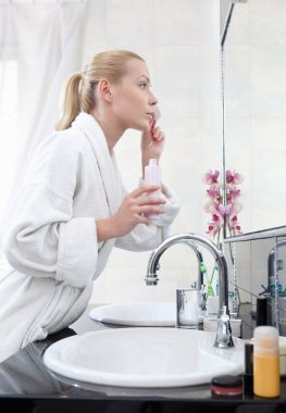 Woman washes face with lotion