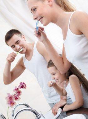 Family of three brush their teeth