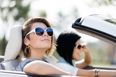 Close up of girls in sunglasses in the white car