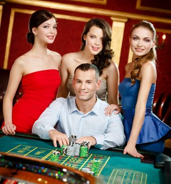 Man surrounded by girls plays roulette