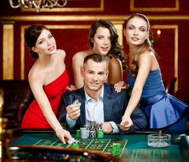 Man surrounded by girls gambles roulette