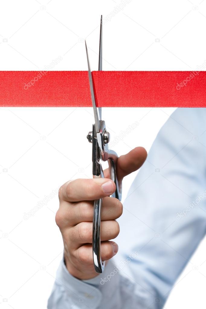 A business man cutting a scarlet satin ribbon