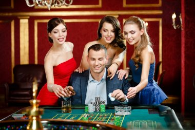 Man surrounded by women plays roulette