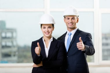 Portrait of two engineers thumbing up