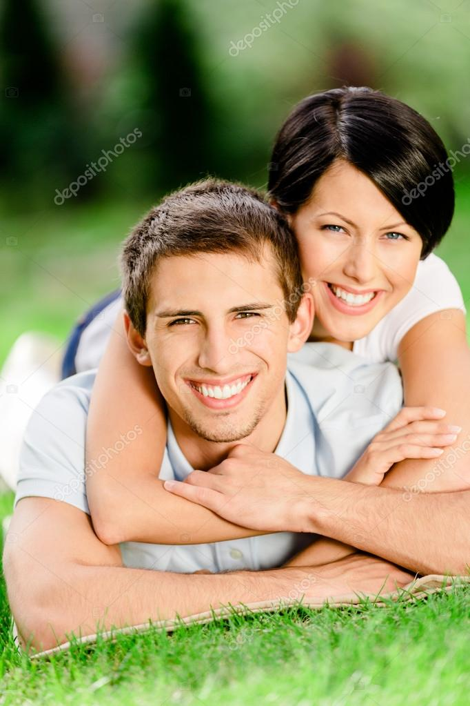 Couple lying on the grass embraces each other