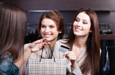 Women pay with credit card and take away bargains