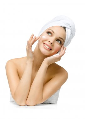 Pretty girl with towel on head applies cream on face