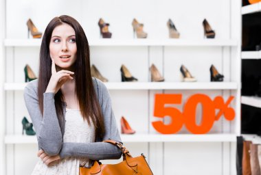Portrait of young woman in shop with 50 percent sale