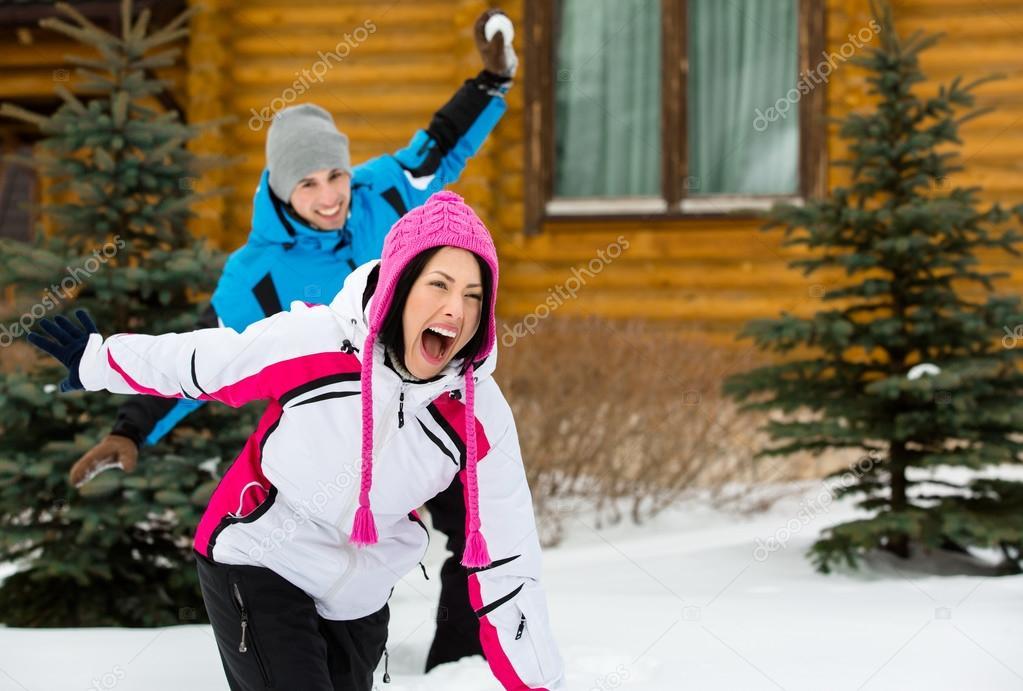 Couple having fun when having snowball fight