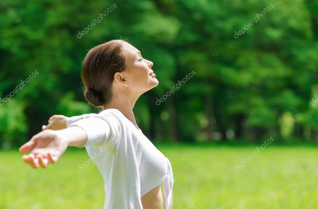 Girl with outstretched arms and eyes closed