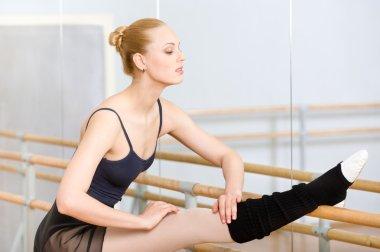 Ballerina stretches herself near barre