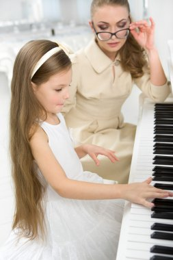 Tutor teaches little girl to play piano