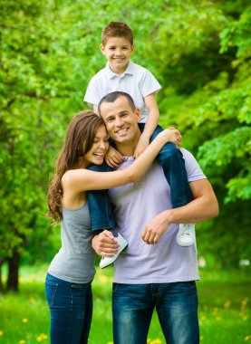 Happy family of three. Dad keeps son on shoulders