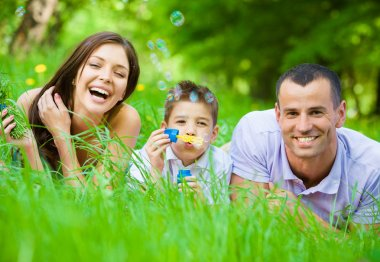 Family of three lying on grass and blows bubbles