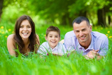 Happy family of three lying on grass with book