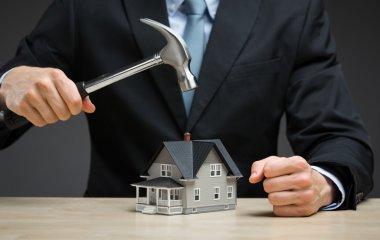 hand keeping hammer over little house