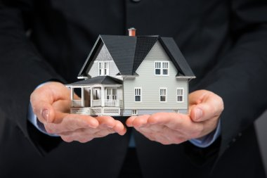 Close up of house model on hands