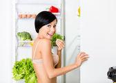 Fotografie dáma jíst u otevřené ledničky