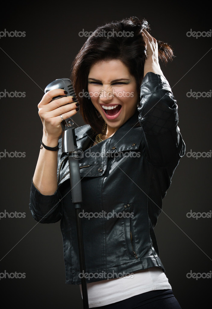 f383c7bae93b Female rock singer holding microphone — Stock Photo © agencyby  39910499