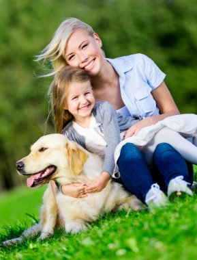 Mother and daughter with dog are on the grass