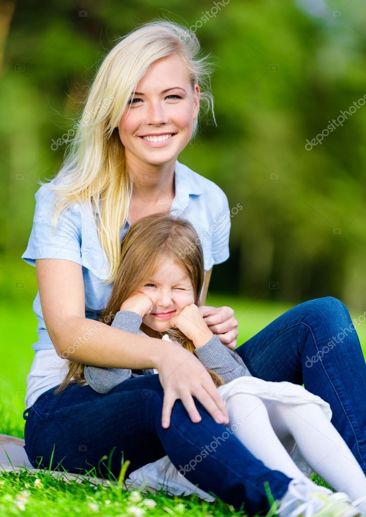 Mother and daughter sitting on the grass