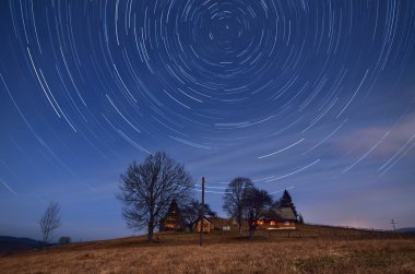 Night landscape with star tracks. Mountain village with wooden houses. Carpathians, Ukraine, Europe stock vector