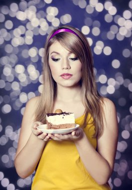 Style teen girl with cake. Photo with bokeh at background.