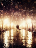 Fotografie Couple walking at alley in night lights. Photo in vintage style.