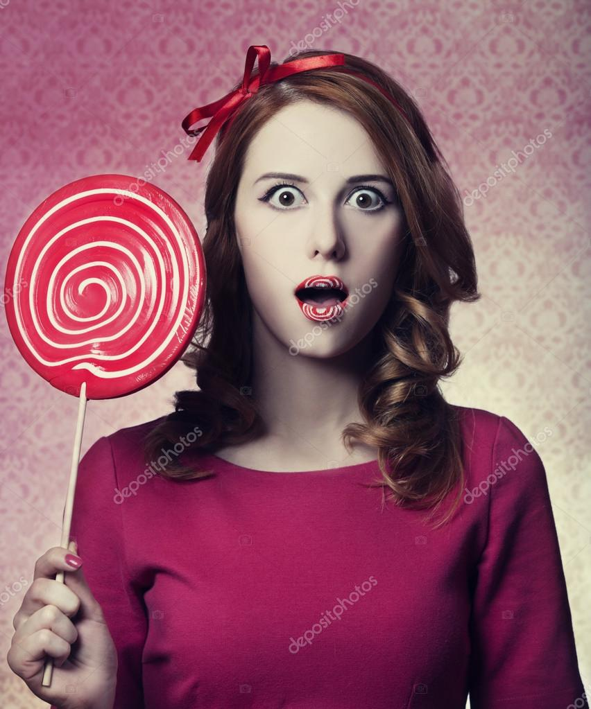 Beautiful redhead girl with lollipop. Photo in retro style.