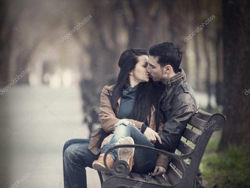 Couple kissing at the bench at alley.