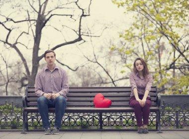 Sad teens sitting at the bench at the park