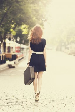 Young woman with suitcase on the city street