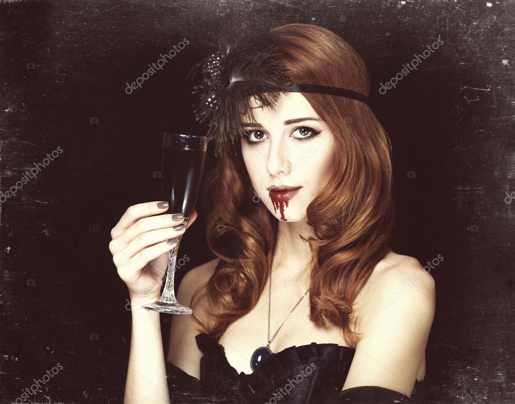Redhead vampire woman with glass of blood. Photo in vintage styl