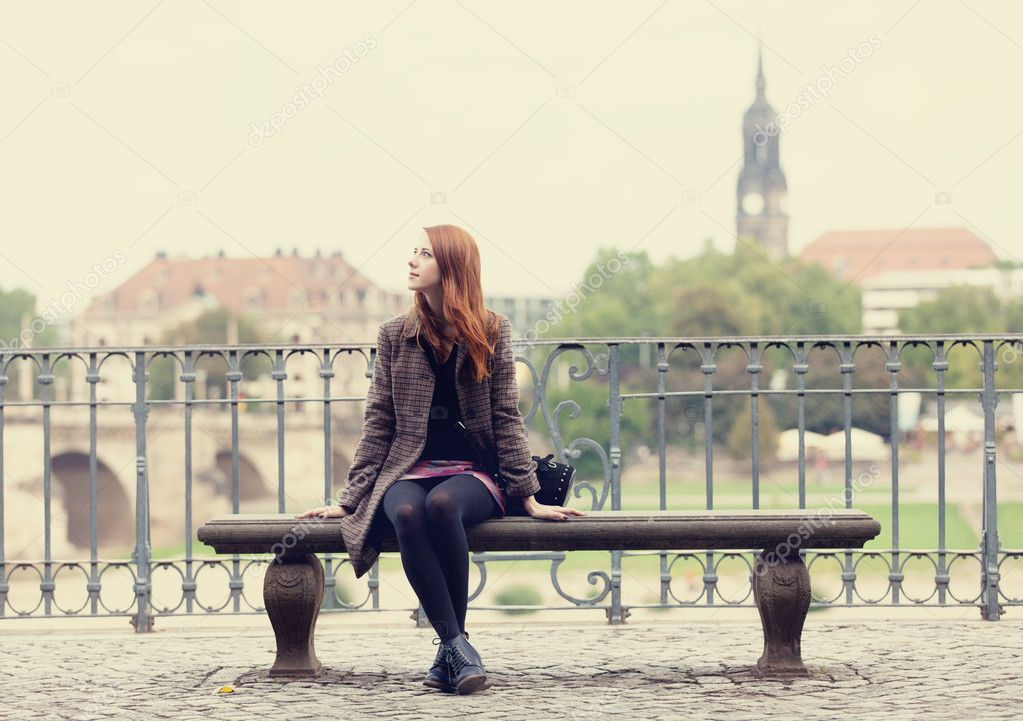 Redhead girl sitting on the bench near river in Dresden.