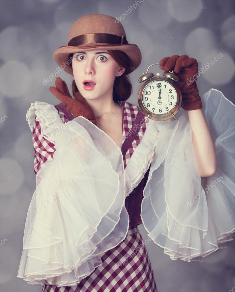 Beautiful redhead women with clock.