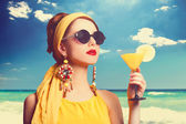 Pěkná zrzka ženy s koktejlem na pláži