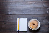 Fotografie Notebook, donut and pencil on wooden table.