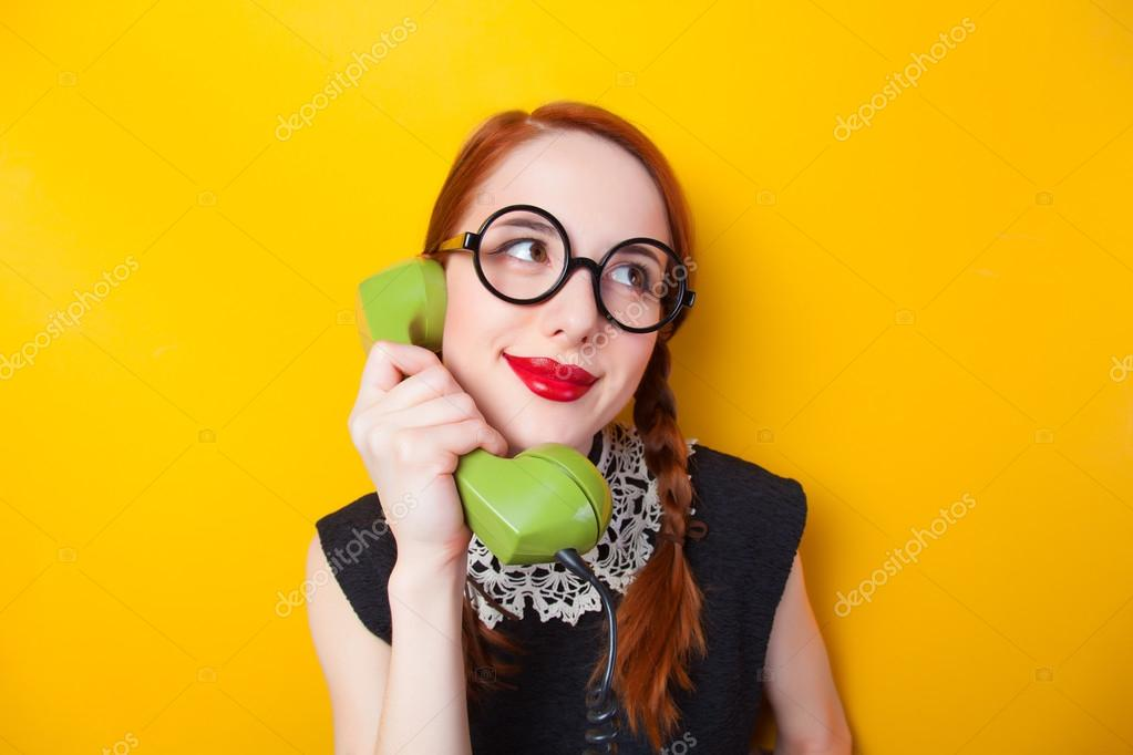 Redhead girl with green phone on yellow background.