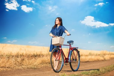 Brunette girl  with bycicle on countryside road.