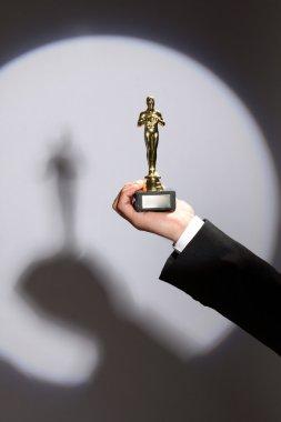 Oscar award in hand