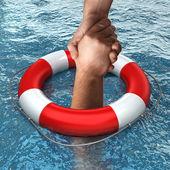 Rote Rettungsboje mit Händen im Wasser